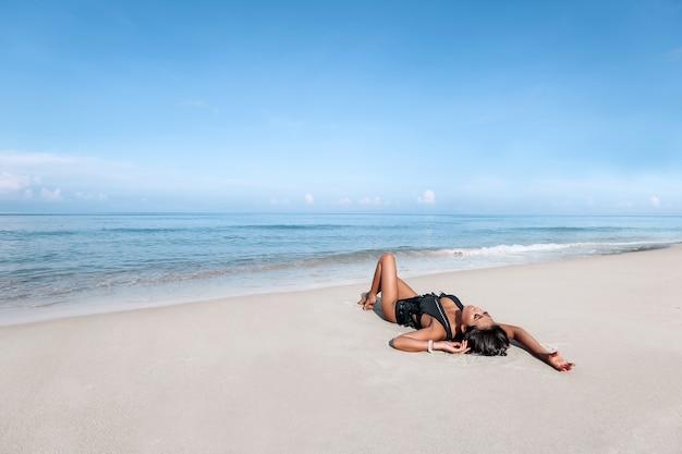 ビーチでポーズをとって若い女性