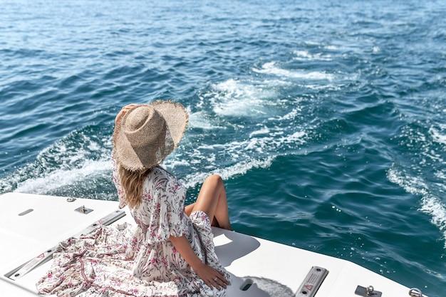ヨットでポーズをとる若い女性