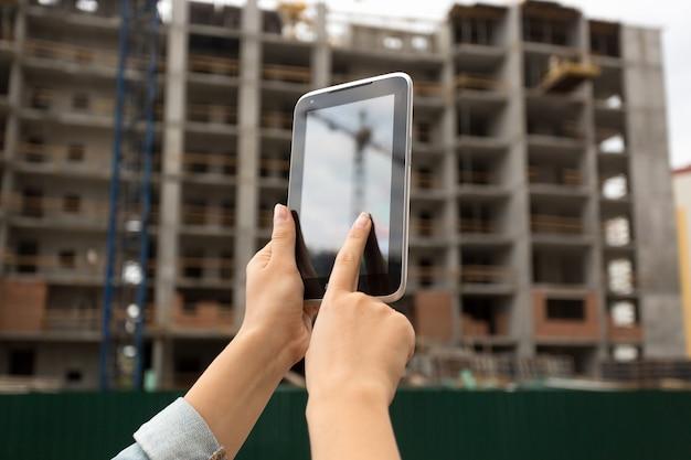 Молодая женщина позирует на строительной площадке и с помощью цифрового планшета