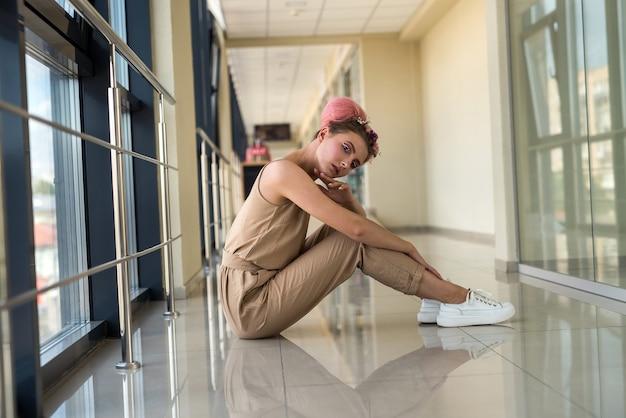 복도에서 바닥에 앉아 카메라에 포즈를 취하는 젊은 여자