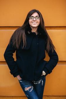 Молодая женщина позирует на городской стене
