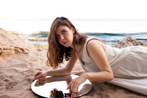 Giovane donna in posa all'aperto su una spiaggia utilizzando uno specchio rotondo