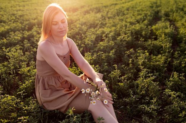 Giovane donna in posa all'aperto in un campo