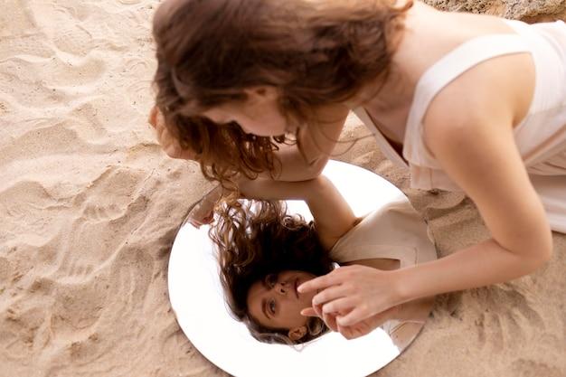 둥근 거울을 사용하여 해변에서 야외에서 포즈를 취하는 젊은 여성