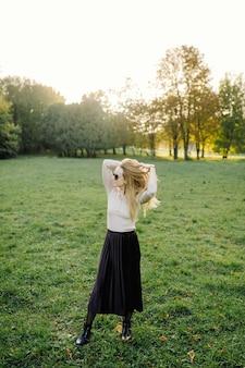Молодая женщина позирует над желтыми листьями в осеннем парке. открытый
