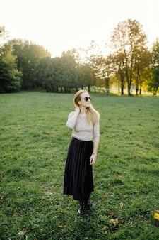 秋の公園で黄色の葉の上にポーズをとる若い女性。アウトドア
