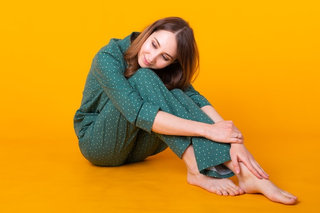 Young woman posing in pajamas on yellow wall