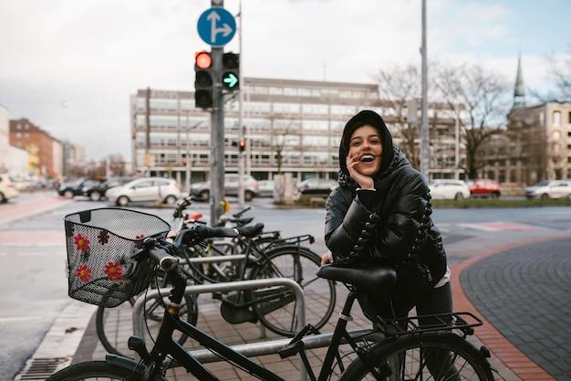 Giovane donna in posa in un parcheggio con le biciclette
