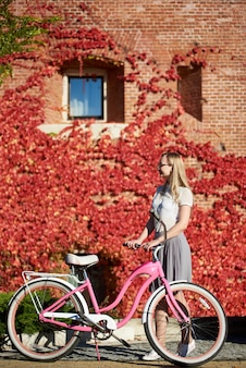 Young woman posing at pink lady bike on bright warm sunny day