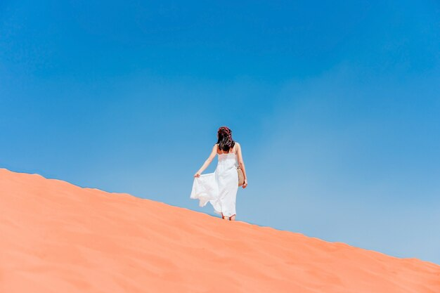 A young woman posing on the ridge of a red sand dune in wadi-rum desert, jordan