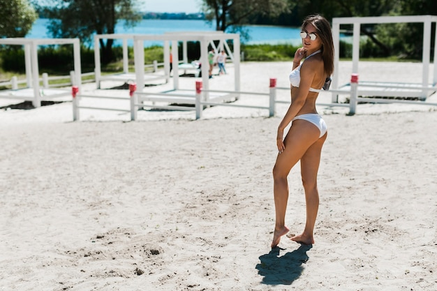 Young woman posing on sandy beach