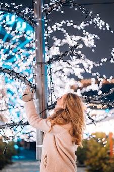 Giovane donna che posa alla via con gli alberi illuminati