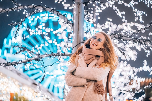Young woman posing at the street with illuminated trees