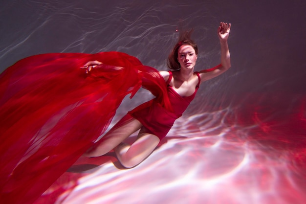 Young woman posing submerged underwater in a flowy dress