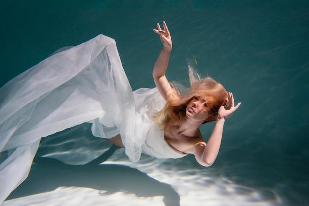 Giovane donna in posa sommersa sott'acqua in un vestito fluido