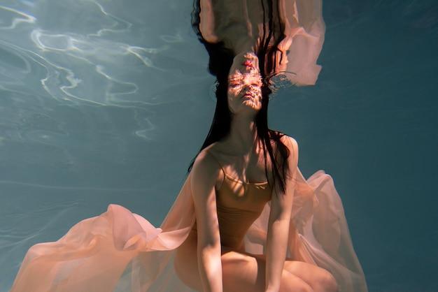 流れるようなドレスを着て水中でポーズをとる若い女性