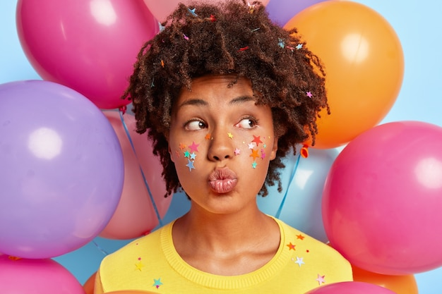 誕生日のカラフルな風船に囲まれてポーズをとる若い女性
