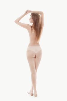 Молодая женщина позирует топлес, идеальная кожа, вид сзади