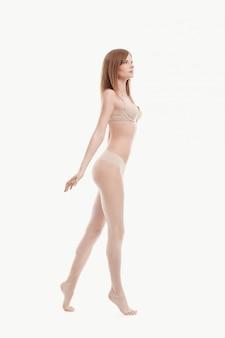 Young woman posing in underwear, beige bra and panties, perfect skin