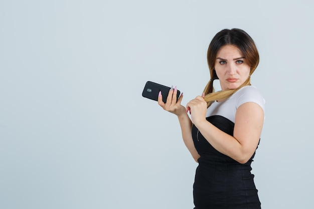 髪を整えて携帯電話を持ってポーズをとる若い女性