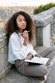 Young woman posing while holding a book