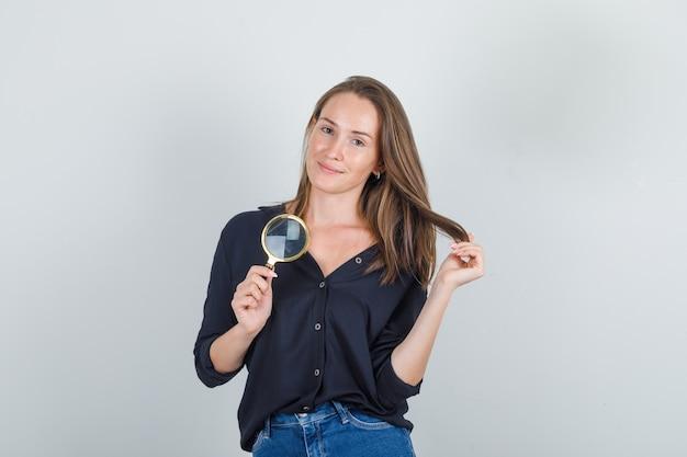 黒いシャツの拡大鏡で髪を保持しながらポーズをとる若い女性