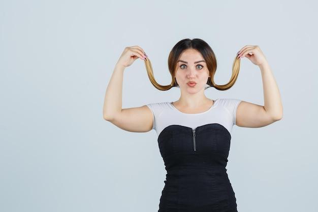 그녀의 머리카락을 잡고 포즈를 취하는 젊은 여자