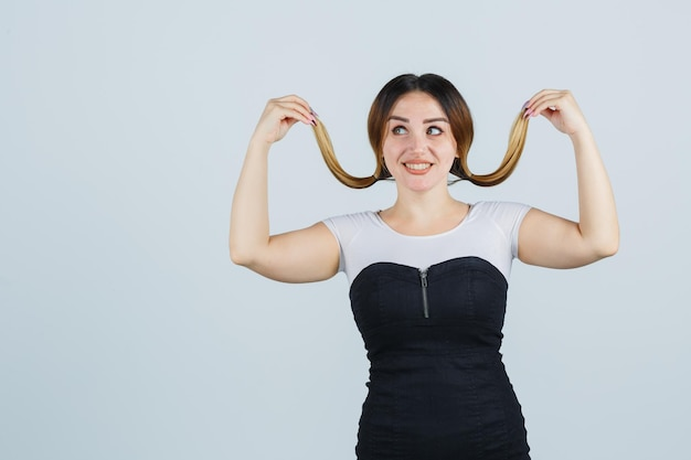 Молодая женщина позирует, держа пряди волос