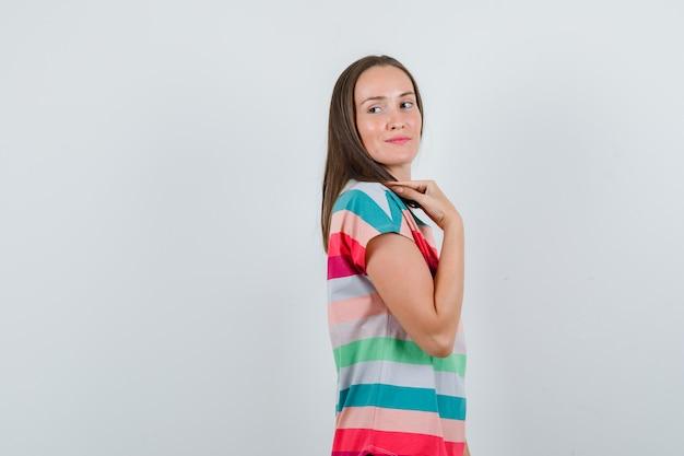 Giovane donna in posa guardando indietro in t-shirt e guardando affascinante. .