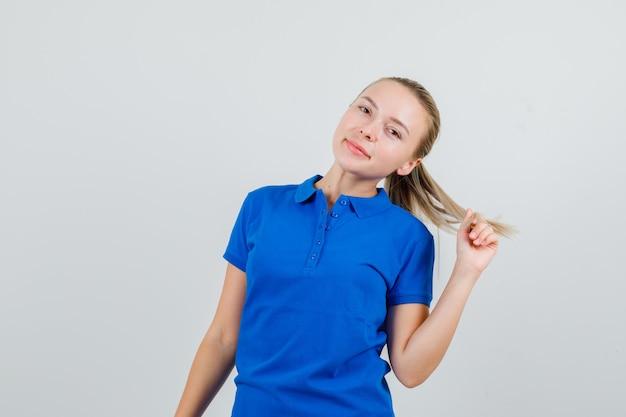 Giovane donna in posa mentre guarda in maglietta blu e sembra affascinante