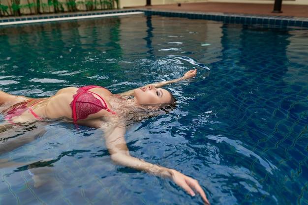 Молодая женщина позирует, лежа в открытом бассейне