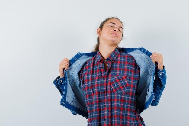 셔츠, 재킷에 그녀의 재킷을 열고 평화로운, 전면보기를 찾고있는 동안 포즈를 취하는 젊은 여자.