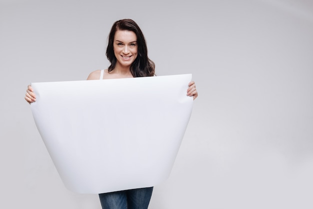 Young woman posing while showing a big blank sheet of paper