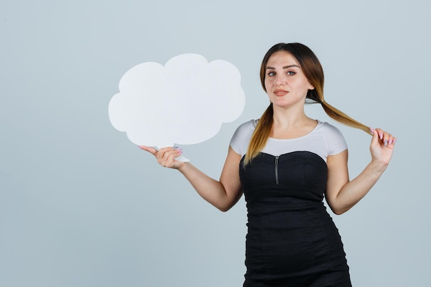 Young woman posing while showing speech bubble