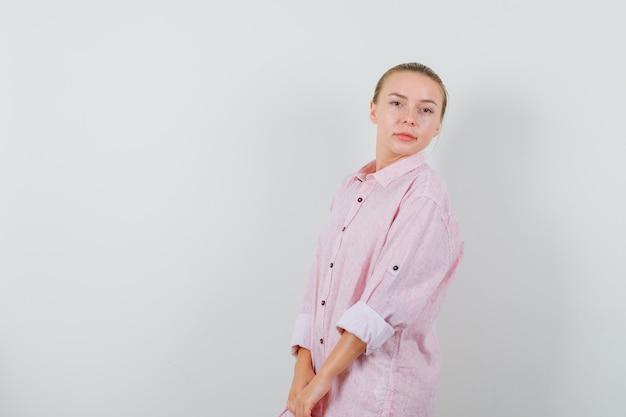 Молодая женщина позирует в розовой рубашке и выглядит восхитительно