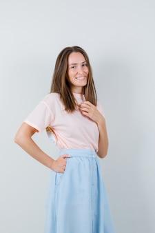 Молодая женщина позирует, стоя в футболке, юбке и выглядит веселой, вид спереди.