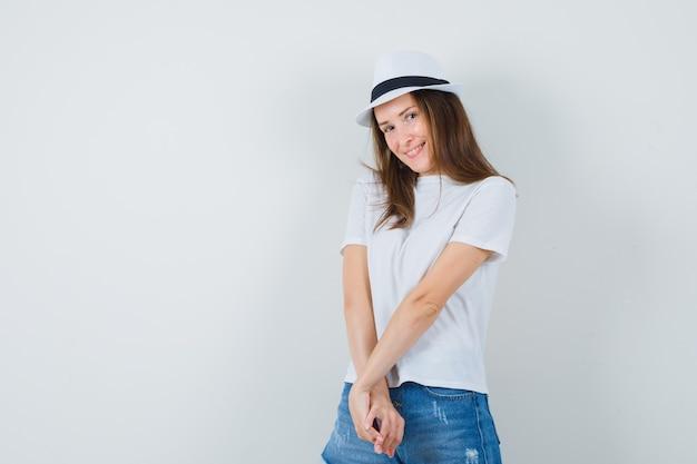 白いtシャツ、ショートパンツ、帽子に立って恥ずかしそうに見ながらポーズをとる若い女性。
