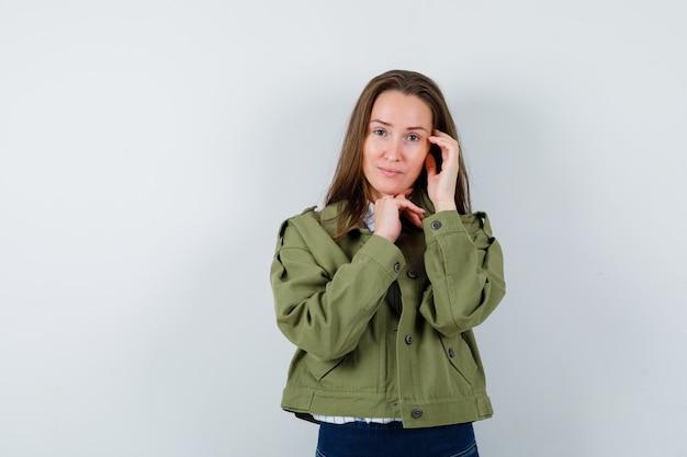 シャツ、ジャケット、優雅に見ながら考えながらポーズをとる若い女性、正面図。