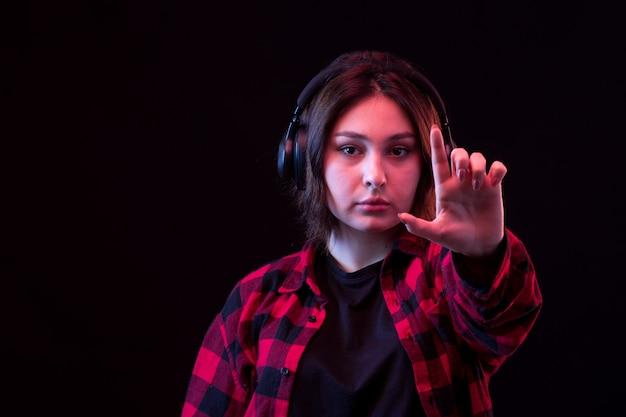 若い女性がヘッドフォンを使用して市松模様の赤と黒のシャツとポーズ