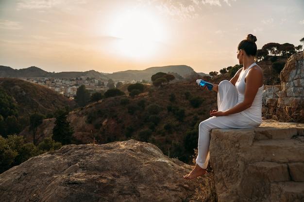 自然の水のボトルでポーズを取る若い女性