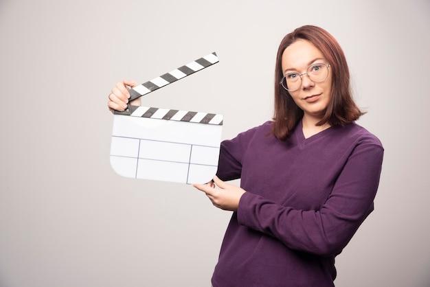 若い女性が白のシネマ テープでポーズします。高品質の写真