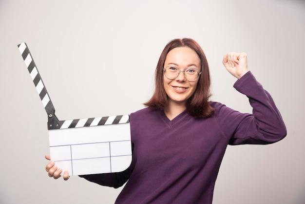 Молодая женщина позирует с лентой кино на белом. фото высокого качества