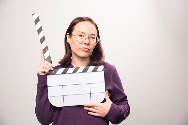 젊은 여자는 흰색에 영화 테이프와 함께 포즈. 고품질 사진