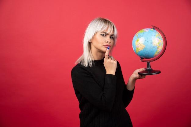 젊은 여자는 빨간색 배경에 지구본과 함께 포즈. 고품질 사진