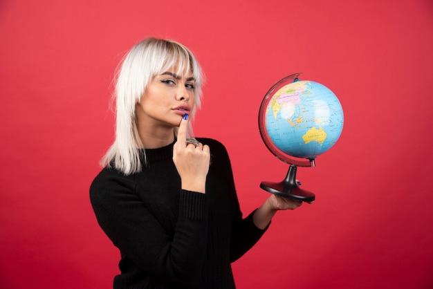 赤い背景に地球儀でポーズをとる若い女性。高品質の写真