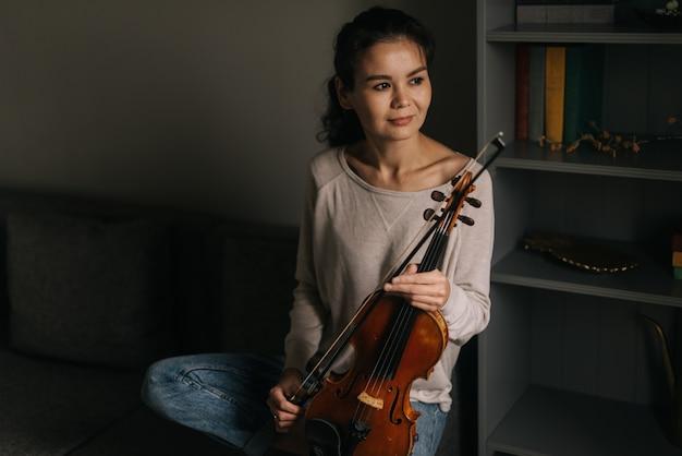 Молодая женщина позирует со скрипкой дома, сидя на диване. девушка позирует с музыкальным инструментом.