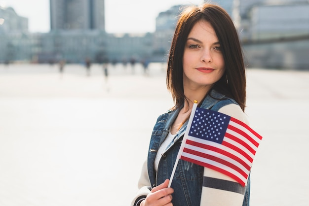 Young woman posing with american flag during fourth of july holiday