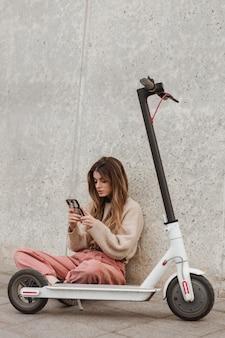 Молодая женщина позирует с электросамокатом