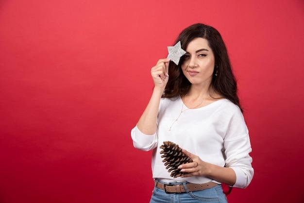 큰 크리스마스 pinecone와 빨간색 배경에 스타 포즈 젊은 여자. 고품질 사진