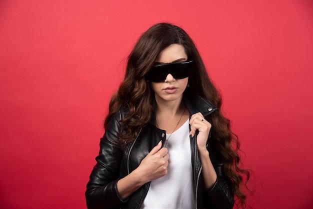 빨간색 배경에 검은 안경 포즈 젊은 여자. 고품질 사진